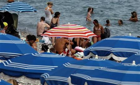 Holiday makers enjoy the beach in Nice, southeastern France, at the start of the summer holidays, July 12, 2011. REUTERS/Eric Gaillard