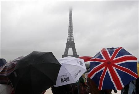 Tourists protect themselves from the rain under umbrellas in front of the Eiffel tower in Paris as they visit the French capital during summer holidays July 19, 2011. REUTERS/Eric Gaillard