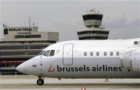 A Brussels airlines aircraft passes along the air traffic control tower and terminal building at Berlin's Tegel airport, August 3, 2011. REUTERS/Fabrizio Bensch