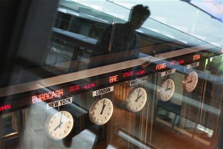 A man reflects in a window as he passes near clocks at the Warsaw Stock Exchange August 9, 2011. REUTERS/Kacper Pempel
