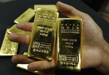 An employee displays one kilogram gold bars during a photo opportunity at the Korea Gold Exchange in Seoul August 9, 2011. REUTERS/Jo Yong-Hak
