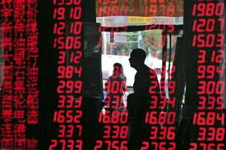 An investor is reflected in a screen showing stock information at a brokerage house in Shenyang, Liaoning province August 10, 2011. REUTERS/Stringer