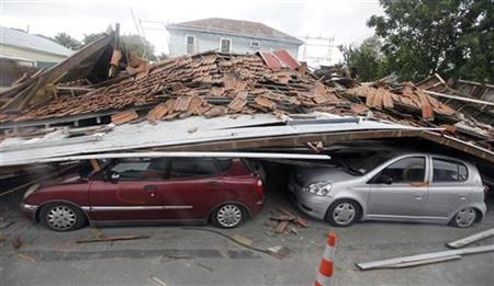 Cars lie crushed under a fallen building in central Christchurch following Tuesday's earthquake February 26, 2011. REUTERS/Mark Baker/Pool