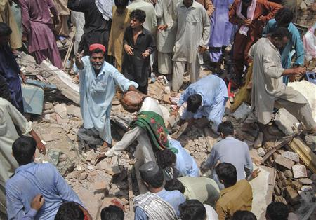 A man shouts for assistance while searching the rubble for survivors at a hotel building which was left destroyed by a bomb blast in the town of Dera Allah Yar, located in the Jaffarabad district of Pakistan's Balochistan province, August 14, 2011. REUTERS/Amir Hussain