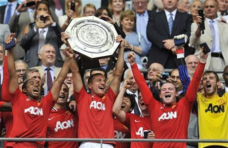 Manchester United's Nemanja Vidic (C) lifts the trophy with teammates after their FA Community Shield soccer match against Manchester City at Wembley Stadium in London August 7, 2011. REUTERS/Toby Melville