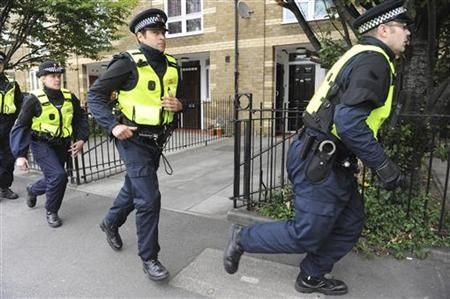 Police officers prepare to raid a property on behalf of detectives conducting investigations into rioting and looting in Hackney, east London August 16, 2011. REUTERS/Ray Collins/POOL