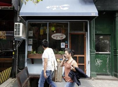 Pedestrians walk past Luke's Lobster restaurant in New York's East Village August 16, 2011. REUTERS/Brendan McDermid