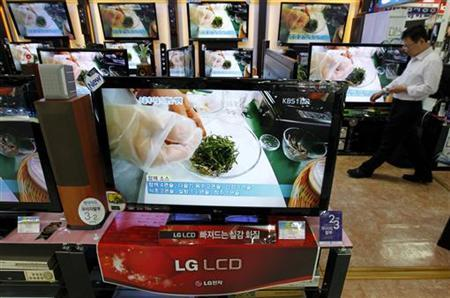 An employee of an electronics shop works behind an LG Electronics' LCD television set (front) in Seoul April 27, 2011. REUTERS/Jo Yong-Hak