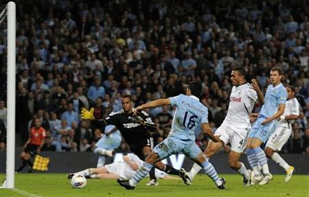 Manchester City's Sergio Aguero (C) shoots to score during their English Premier League soccer match against Swansea City at the Etihad stadium in Manchester, northern England August 15, 2011. REUTERS/Nigel Roddis