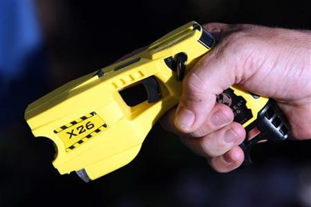 A municipal policeman in Nice poses with the Taser X26 model during a presentation in Nice, south eastern France May 27, 2010. REUTERS/Sebastien Nogier