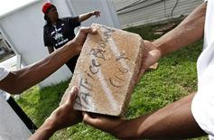 <p>Diane Latiker gives direction to teens passing around paving stones painted with the names of kids killed by violence as they repair a memorial for the victims of violence in Chicago August 3, 2011. REUTERS/Jim Young</p>