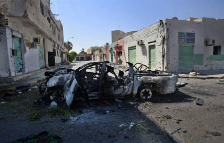 A destroyed vehicle sits on the side of the road after Libyan rebel fighters pushed pro-Gaddafi forces out of the center of the strategic coastal city of Zawiyah, August 20, 2011.   REUTERS/Bob Strong
