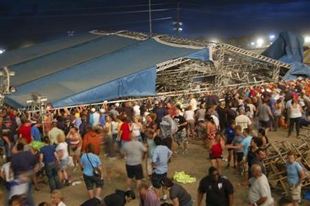 Concertgoers and emergency personnel hold up the stage roof and rigging after it collapsed minutes before a concert by Sugarland at the Indiana State Fairgrounds in Indianapolis August 13, 2011. REUTERS/Steve Baker