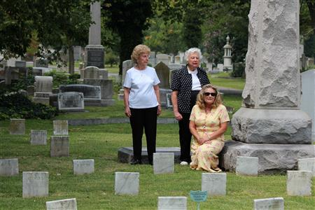 Alma Lewis (L), Mary Williams (C) and Karen Cole (kneeling), members of the Pickett-Buchanan chapter of the United Daughters of the Confederacy, visit the graves of Confederate soldiers at Norfolk's Elmwood Cemetery on August 18, 2011. REUTERS/Matthew Ward/Handout