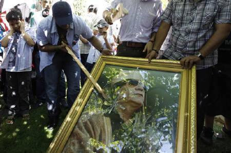 Demonstrators smash a poster of Libyan leader Muammar Gaddafi during a protest against Gaddafi outside of the Libyan embassy in Ankara August 22, 2011. REUTERS/Umit Bektas