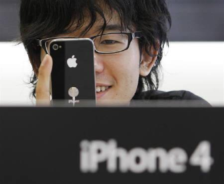 A customer tries out the new iPhone 4 at Apple Inc's store in the Ginza district of Tokyo June 24, 2010. REUTERS/Yuriko Nakao/Files