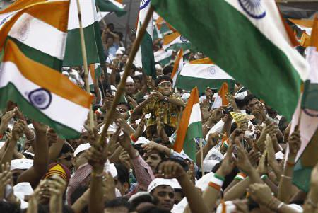 Supporters of veteran social activist Anna Hazare shout slogans as they wave national flags on the seventh day of Hazare's fast at Ramlila grounds in New Delhi August 22, 2011. REUTERS/Adnan Abidi