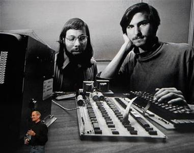 Steve Jobs stands beneath a photograph of him and Apple-co founder Steve Wozniak from the early days of Apple during the launch of Apple's new ''iPad'' tablet computing device in San Francisco, California, January 27, 2010. REUTERS/Kimberly White