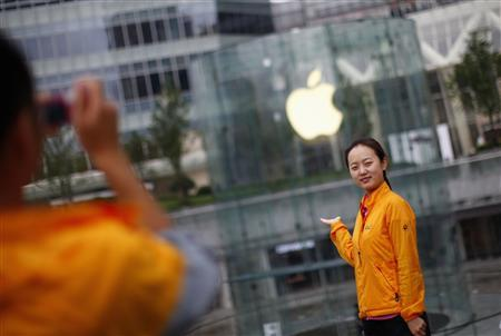 A woman poses in front of an Apple retail store at the financial district in Shanghai August 25, 2011. REUTERS/Carlos Barria