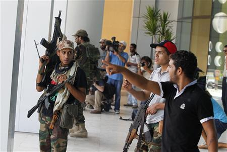 Rebel fighters take up positions during gunfight with sniper loyal to Muammar Gaddafi near the Corinthia Hotel in Tripoli August 25, 2011. REUTERS/Louafi Larbi