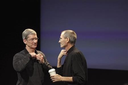 Tim Cook and Steve Jobs remove their microphones after a news conference at Apple headquarters in Cupertino, July 16, 2010. REUTERS/Kim White