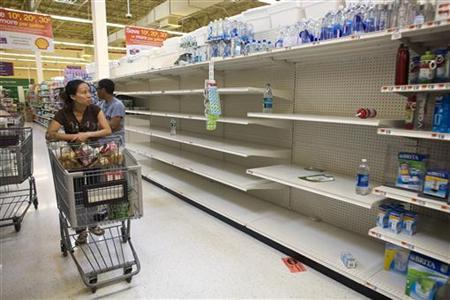 A shopper passes by empty shelves while looking for bottled water at a Stop and Shop at Rockaway Beach in New York, August 26, 2011. REUTERS/Allison Joyce