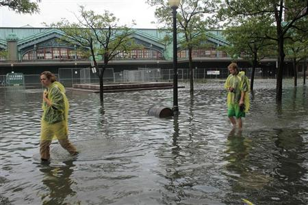 People walk through flooded streets after the pass of Hurricane Irene at Hoboken, New Jersey August 28, 2011. REUTERS/Eduardo Munoz
