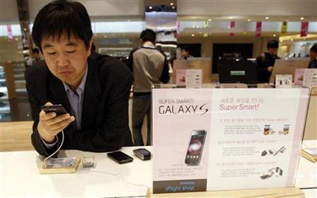 A customer looks at a Samsung Electronics mobile phone on display at a Samsung Electronics shop at the company's headquarters in Seoul April 29, 2011. REUTERS/Truth Leem