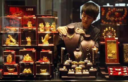 An employee adjusts a gold necklace on a displaying model near glass cases containing gold figurines at a gold shop in Wuhan, Hubei province August 25, 2011. REUTERS/Stringer