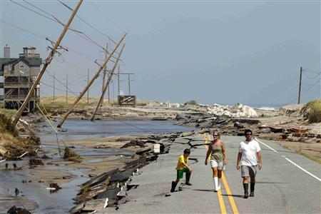 Residents walk along Hwy 12, the main road that connects Cape Hatteras National Seashore to the mainland, after it was destroyed by Hurricane Irene in Rodanthe, North Carolina, August 28, 2011. REUTERS/Jose Luis Magana
