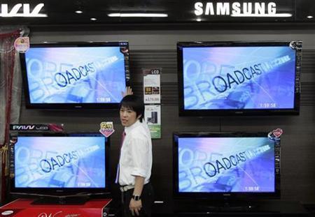 An electronics shop salesperson sells flat screen TVs of Samsung Electronics displayed at a shop in Seoul October 6, 2009. REUTERS/Choi Bu-Seok
