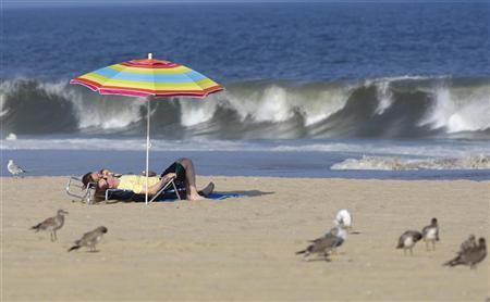 Two people lie down at the beach as Hurricane Irene approaches, in Asbury Park, New Jersey August 26, 2011. REUTERS/Chip East
