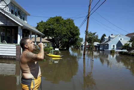 A man drinks beer as he waits for flooding to subside inside of his home in the town of Totowa, New Jersey August 30, 2011. REUTERS/Lucas Jackson