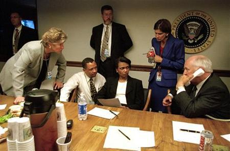 Vice President Dick Cheney speaks to President George W. Bush by phone inside the operations center at the White House with staff, September 11, 2001. REUTERS/White House photo/David Bohrer