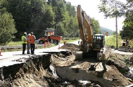 Vermont Transportation Agency workers repair a section of Route 100 in Waitsfield, Vermont, after it was washed away when Hurricane Irene struck the area earlier this week, August 31, 2011. REUTERS /Herb Swanson