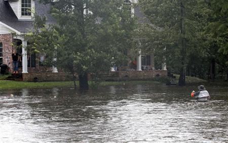Rick Porche (bottom right) walks through his flooded yard as Tropical Storm Lee slowly makes landfall in Lafitte, Louisiana USA on September 4, 2011. REUTERS/Dan Anderson