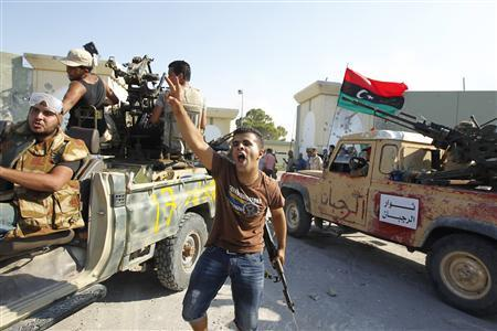 Libyan rebel fighters celebrate after their entering the Bab al Aziziya compound in Tripoli August 23, 2011. REUTERS/Zohra Bensemra