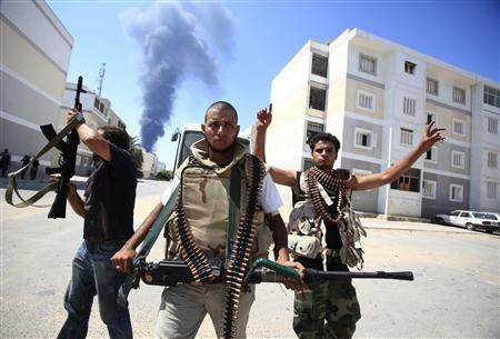 Libyan rebel fighters react as they search for snipers while fighting for the final push to flush out Muammar Gaddafi's forces in Abu Slim area in Tripoli, August 25, 2011. REUTERS/Zohra Bensemra