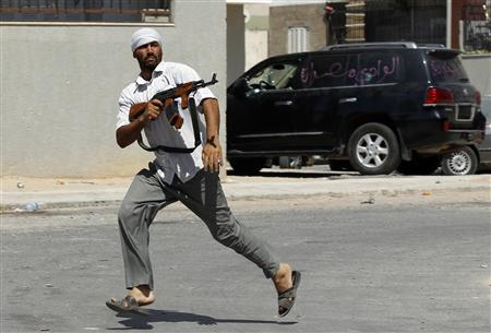 A rebel fighter fires his rifle as he runs across a street in Tripoli, August 25, 2011. REUTERS/Goran Tomasevic
