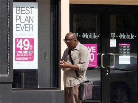 A man checks his mobile phone as he walks past a T-Mobile store in downtown Los Angeles, August 31, 2011. REUTERS/Fred Prouser