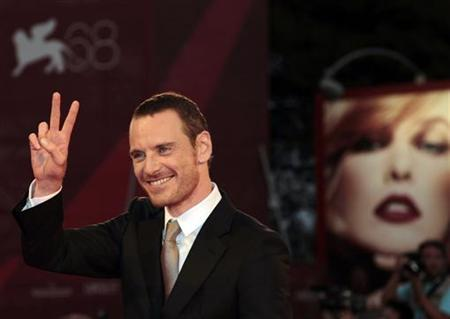 Actor Michael Fassbender gestures as he arrives on the red carpet for the film ''A Dangerous Method'' directed by director David Cronenberg at the 68th Venice Film Festival September 2, 2011. REUTERS/Alessandro Bianchi