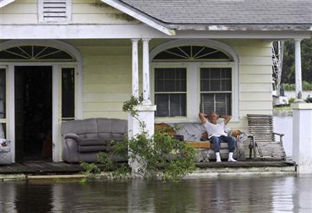 A man sits on his front porch while flood waters reach outside his house as Tropical Storm Lee slowly makes landfall in Lafitte, Louisiana, September 4, 2011. REUTERS/Dan Anderson