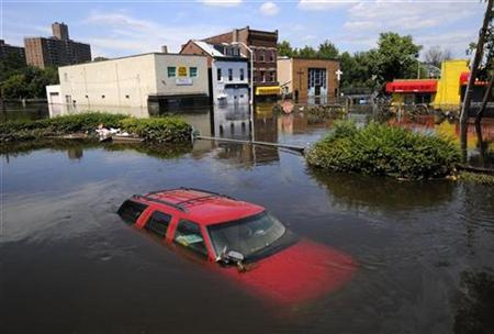 Flood waters from the Passaic River fill the streets covering automobiles including a Chevrolet SUV days after Hurricane Irene in Paterson, New Jersey, August 31, 2011. REUTERS/Mark Dye