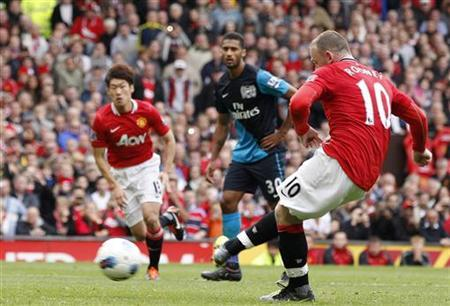 Manchester United's Wayne Rooney (R) scores from a penalty against Arsenal during their English Premier League soccer match at Old Trafford in Manchester, northern England, August 28, 2011. REUTERS/Darren Staples