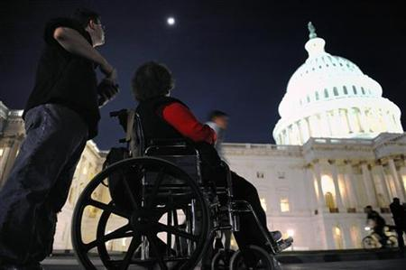 A woman in a wheelchair and her son are just a few of thousands of protestors remain late in the evening after a rally against President Barack Obama's health care legislation, on the grounds of the US Capitol in Washington, March 20, 2010. REUTERS/Jonathan Ernst