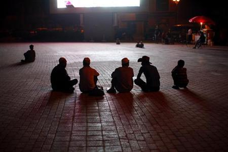 Ethnic Uighur men sit in front of a television screen at a square in Kashgar, Xinjiang province August 2, 2011. REUTERS/Carlos Barria