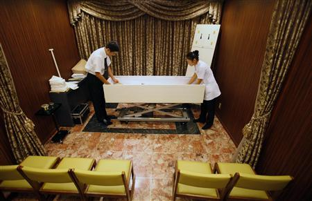 Morticians prepare a body at the Lastel corpse hotel in Yokohama, south of Tokyo, September 10, 2011. Death is a rare booming market in stagnant Japan and the Lastel corpse hotel, where bereaved families can check in their dead while they wait their turn in the queue for one of the city's overworked crematoriums, is just one example of how businessmen are trying to tap it. REUTERS/Yuriko Nakao