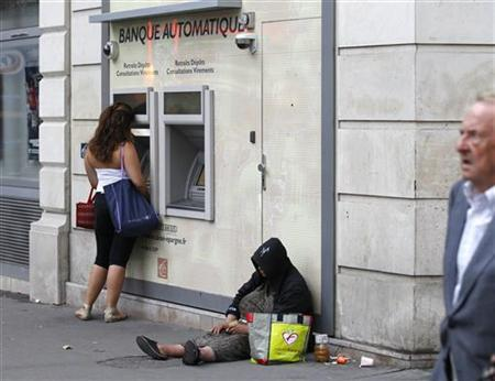 An homeless woman sits on a footpath while a person withdraws money from an ATM along a main road in central Paris August 22, 2011. REUTERS/Yves Herman
