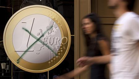 People walk past a pizza shop with a sign of a euro coin which was crossed out in central Madrid, September 13, 2011. REUTERS/Paul Hanna