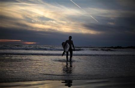 A surfer walks out of the ocean as the sun sets on New Year's Eve on Venice Beach in Los Angeles, California, December 31, 2010. REUTERS/Lucy Nicholson